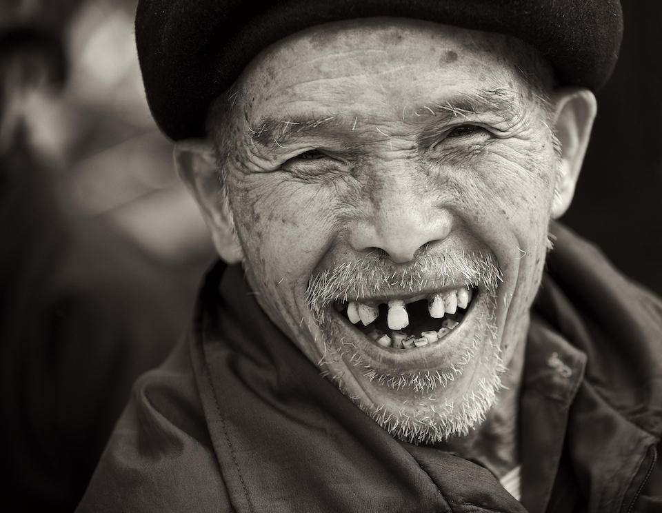 A mand smiles in the Dong Van Sunday market in Vietnam. Image by New Orleans based travel photographer, Marc Pagani