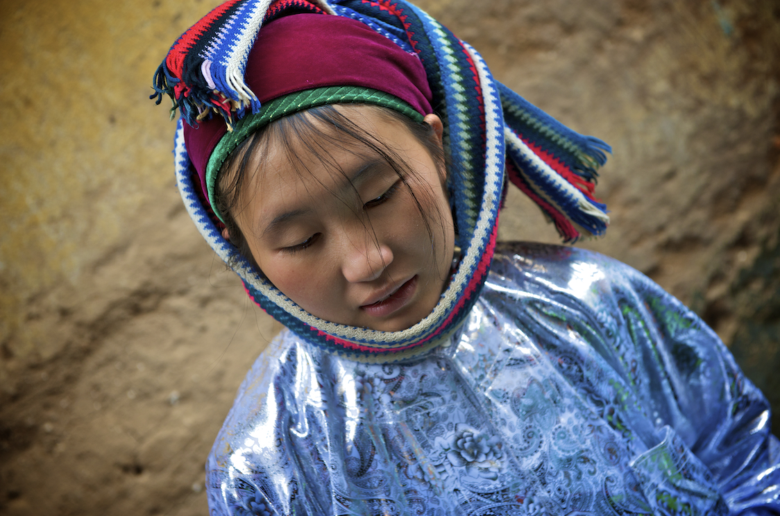 A young H'Mong girl in the Dong Van market in Vietnam.  Image by New Orleans based travel photographer, Marc Pagani
