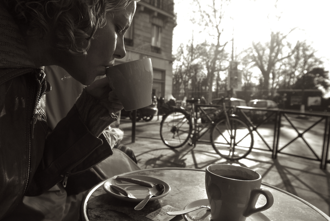 A woman sips coffee at a café in Paris.  Image by New Orleans based travel photographer, Marc Pagani - marcpagani.com