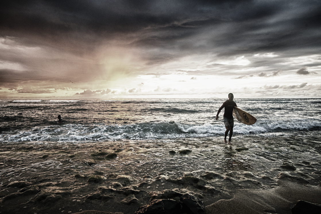 a surfer exits the water in Rincon, Puerto Rico.  Image by New Orleans based travel photographer, Marc Pagani - marcpagani.com