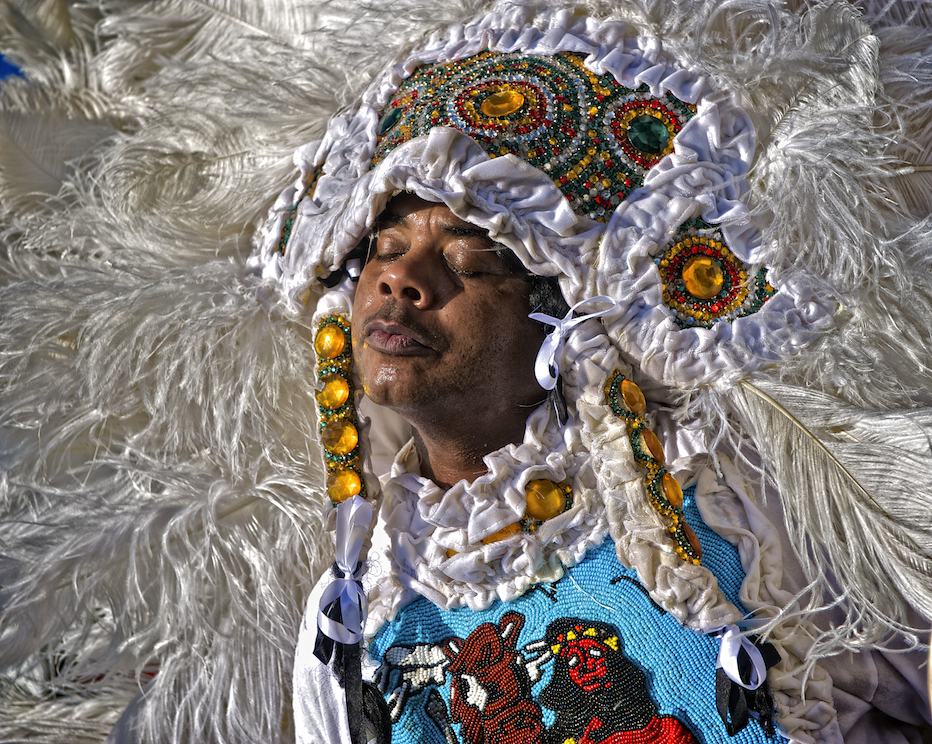 a Mardi Gras Indian enjoys the sun in New Orleans.  Image by New Orleans based travel photographer, Marc Pagani