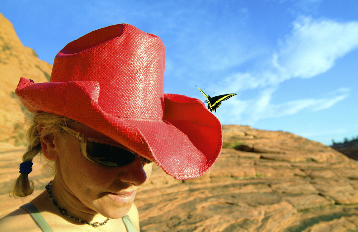 A butterfly lands on the red cowboy hat of a climber in Red Rock Canyon, Nevada. Image by New Orleans based travel photographer, Marc Pagani - marcpagani.com