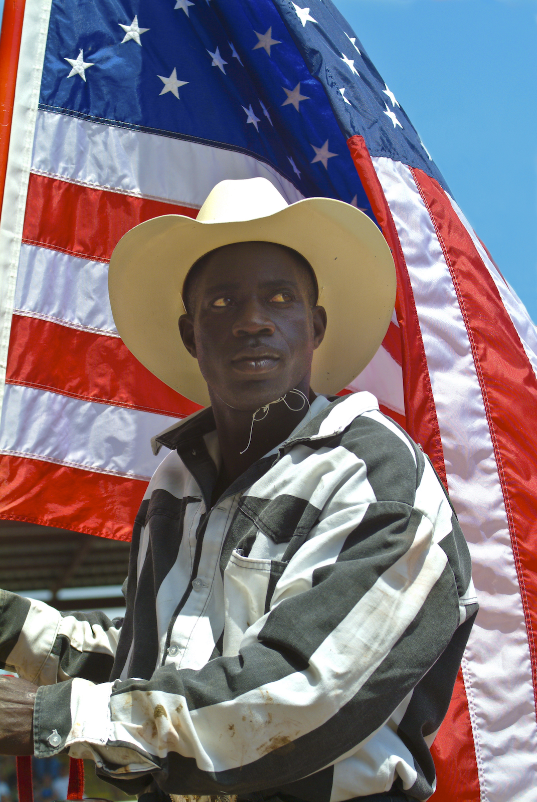 A prisoner poses in front of the American flag at the Angola Prison Rodeo in Louisiana.  Image by New Orleans based travel photographer, Marc Pagani - marcpagani.com