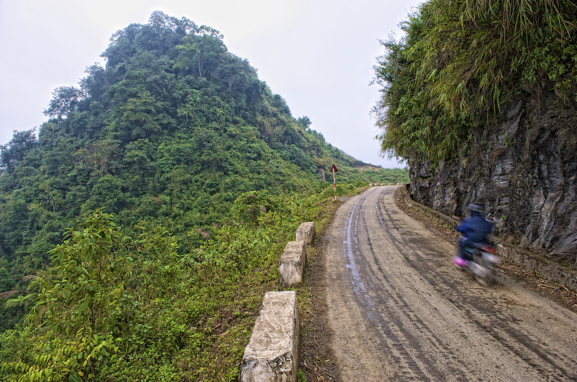 A motorcyclist speeds by in northeastern Vietnam.  Image by New Orleans based travel photographer, Marc Pagani