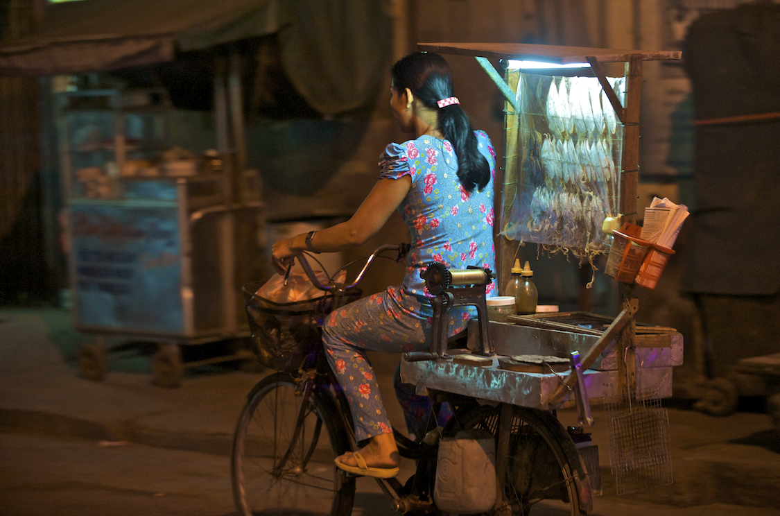A fishmonger rides her bike through Ho Chi Minh City in Vietnam.  Image by New Orleans based travel photographer, Marc Pagani - marcpagani.com