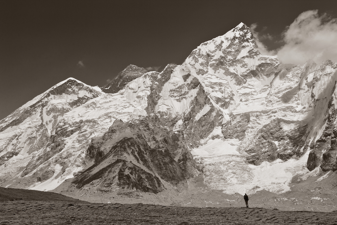 A climber stands in front of Ama Dablam and Mount Everest after climbing Kala Pattar in the Nepal Himalayas.  Image by New Orleans based travel photographer, Marc Pagani - marcpagani.com