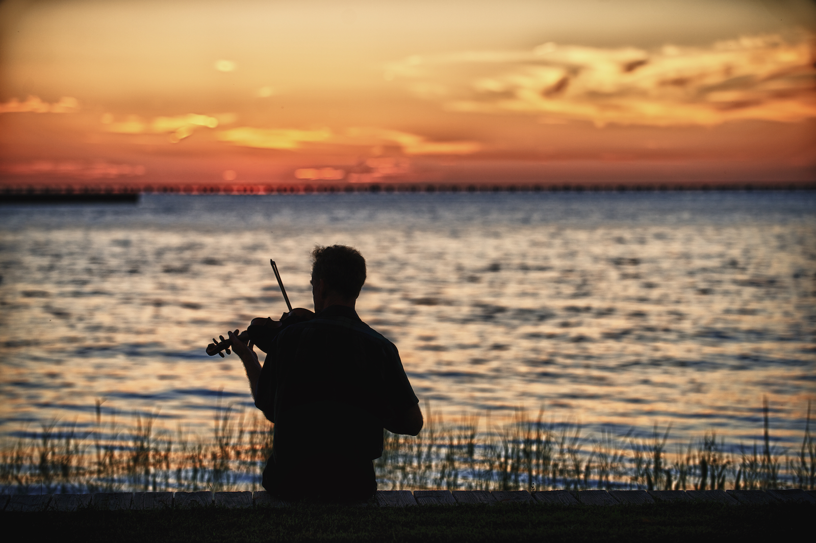 A mand plays fiddle on the north shore of Lake Pontchartrain in Louisiana.  Image by New Orleans based travel photographer, Marc Pagani