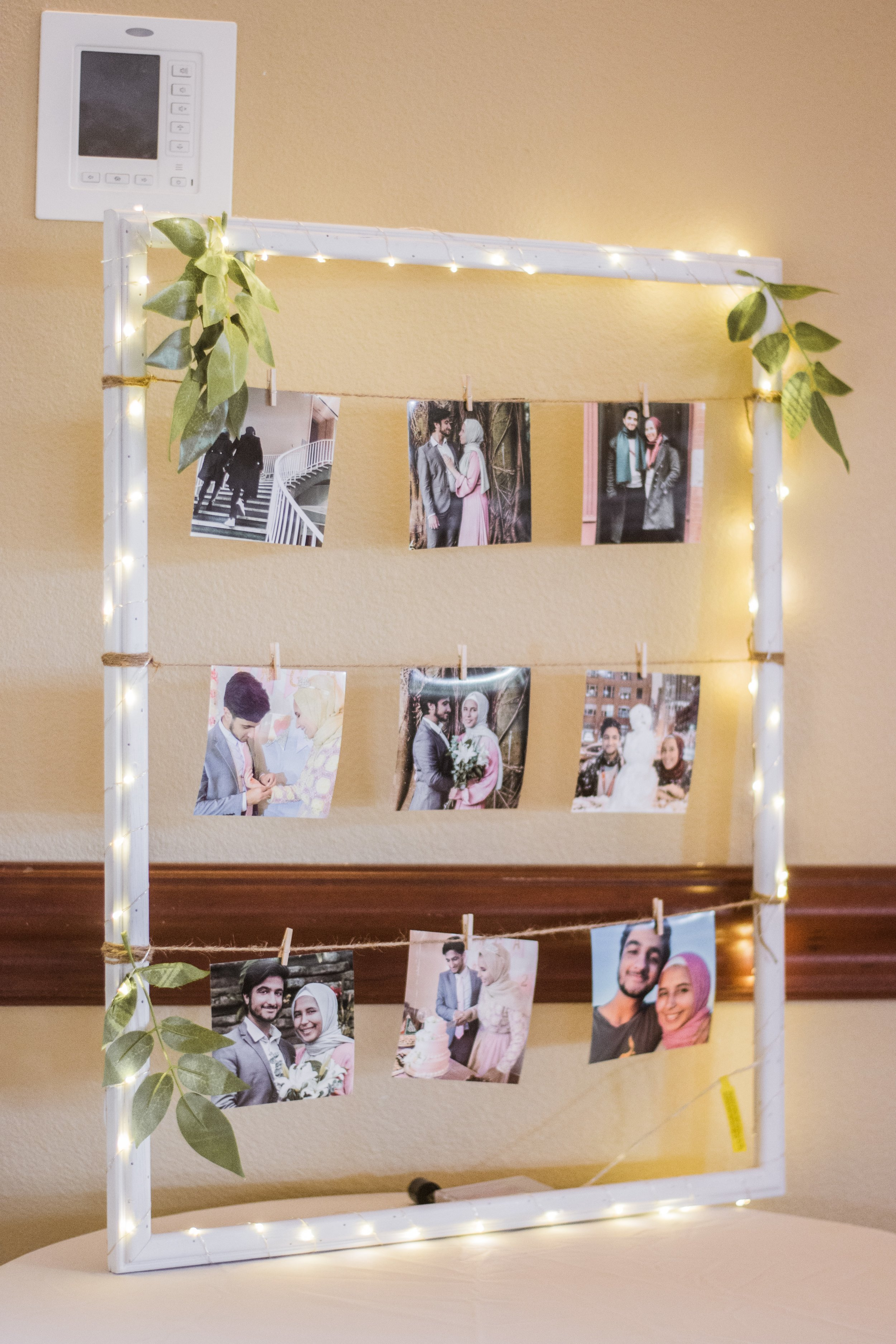 A DIY project we made by taking a frame from the thrift store, spray painting it, wrapping fairy lights around, and tying twine with mini clips to hold the pictures.