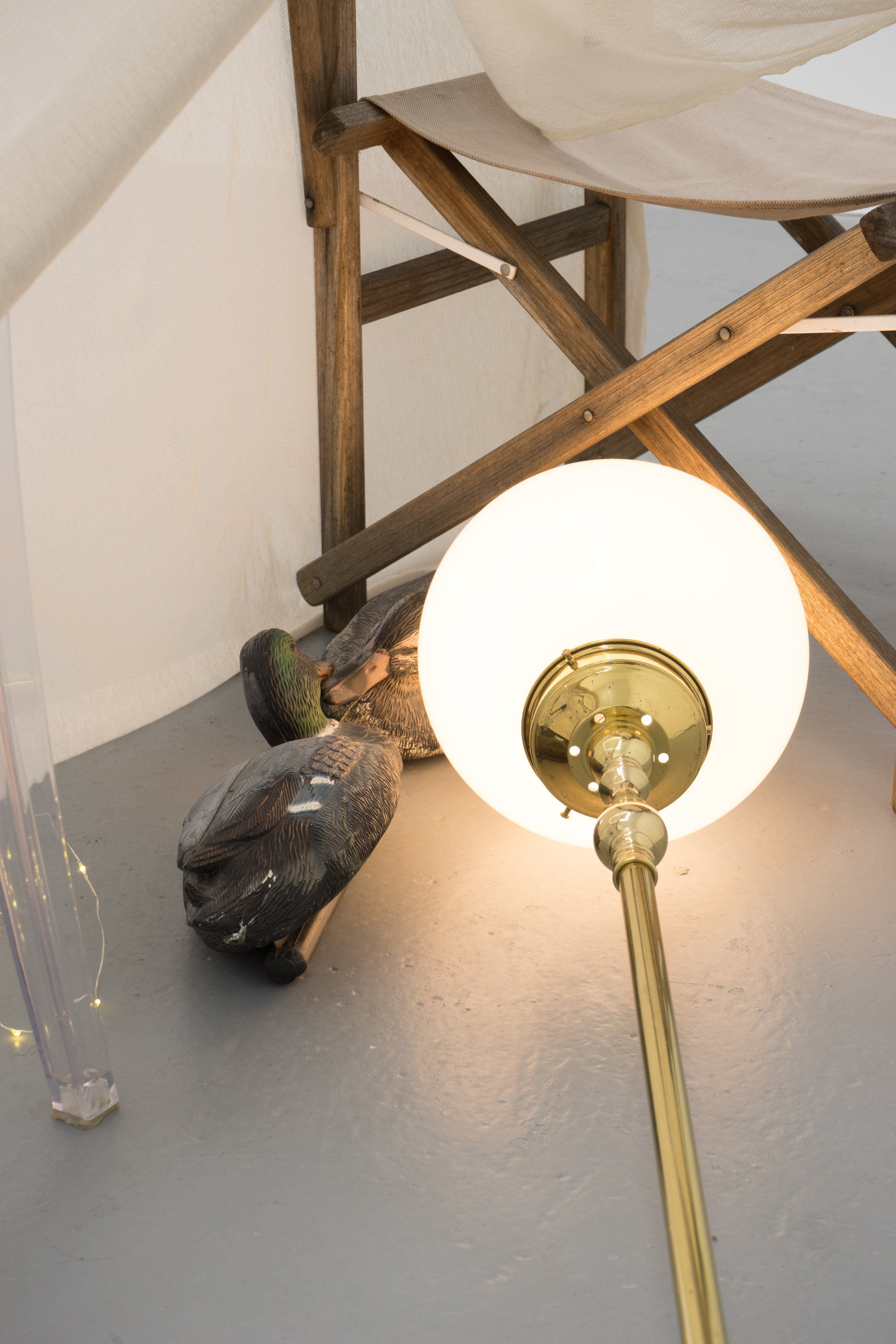 Kate Meakin  Starry Night , 2018 Roll of jersey, deck chair, replica 'Ghost Chair', vintage brass lamp, plastic decoy ducks, LED fairy lights, antique lace  Image credit: Ruben Bull-milne
