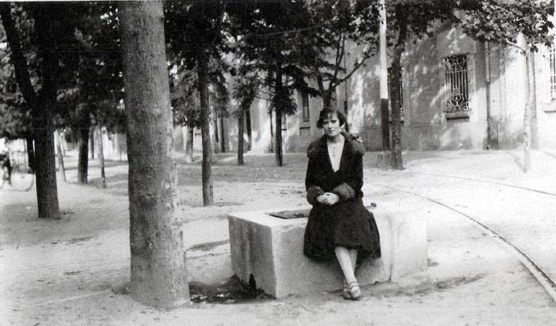 Foto antigua de la Plaza de Ciudad Lineal. Chica sentada sobre un banco-fuente.