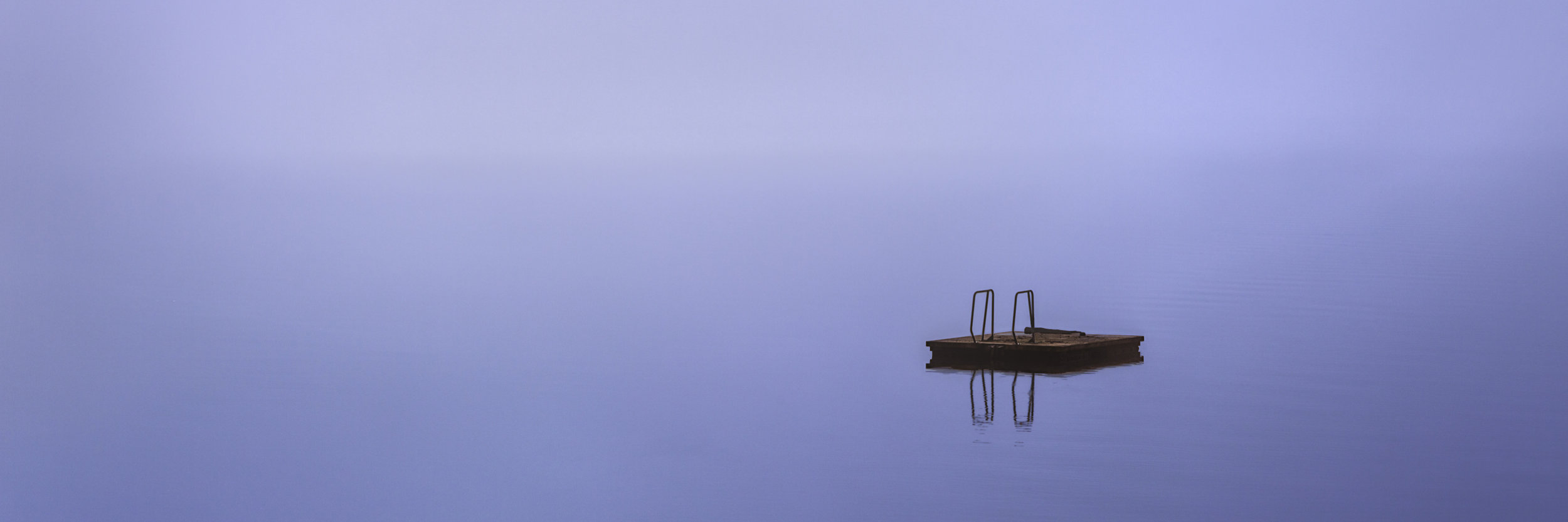 A panoramic photograph of a dock floating on perfectly still water of the Hood Canal. The clam scene is flooded with a morning fog that blends the sky and the water in a seamless blue canvas.