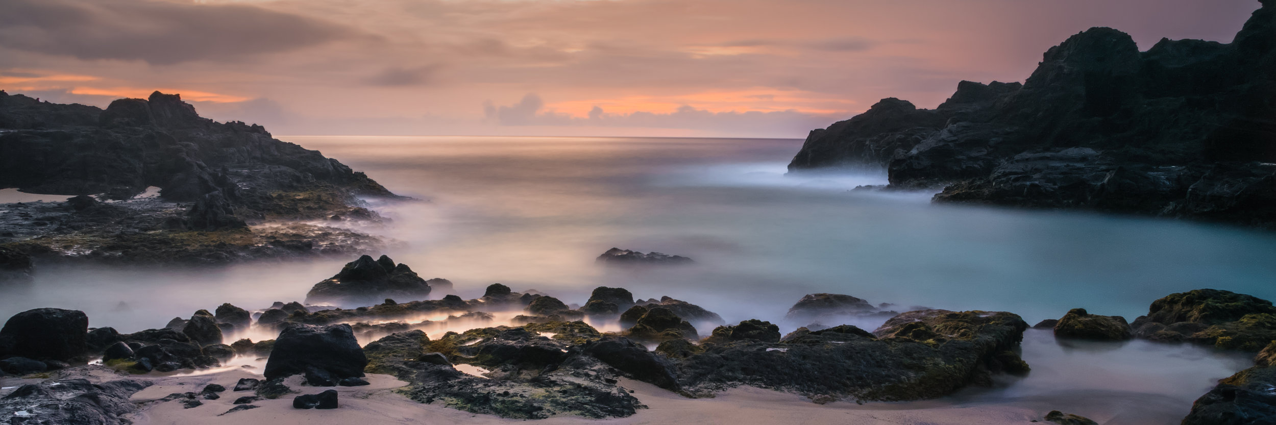 Eternity Beach is a fine art photograph of Halona Beach Cove on the island of Oahu, Hawaii by Jason Matias. It is a panoramic, long exposure with oranges, salmons, pinks, blues and lava rock.