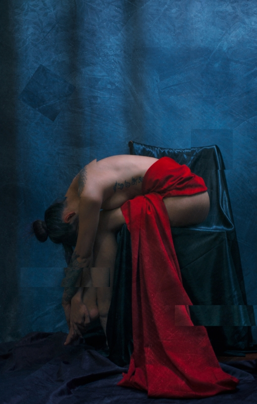 """Fine art nude photograph by Jason Matias of a beautiful woman in a bent over, but powerful pose. The photograph is dynamic with contrasting red and blue cloth and warm - cold composition. The female model is has body art tattoos: wings on her upper back. """"STRENGTH"""" tattooed down her side and a half sleeve of the Green Man. There is a wonderful texture and abstraction in the image. Six sections of the photograph have been lifted and juxtaposed."""
