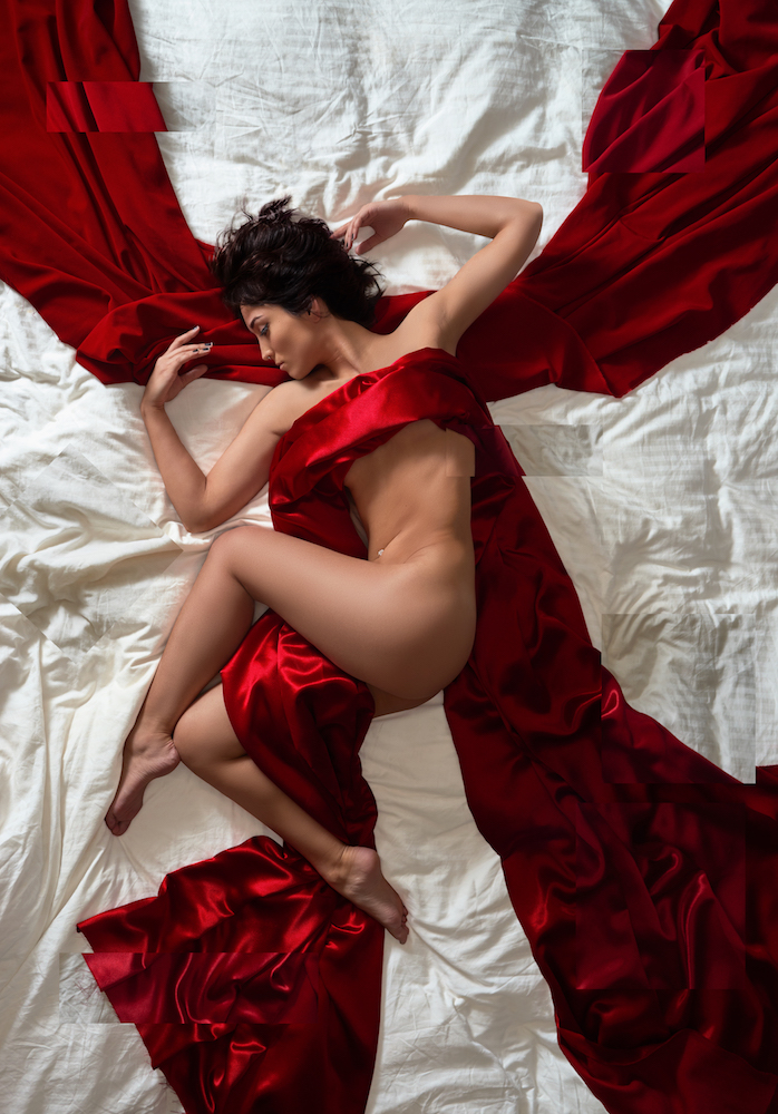 Fine art nude photograph by Jason Matias of a beautiful woman wrapped in red satin and silk on a white bedding background.