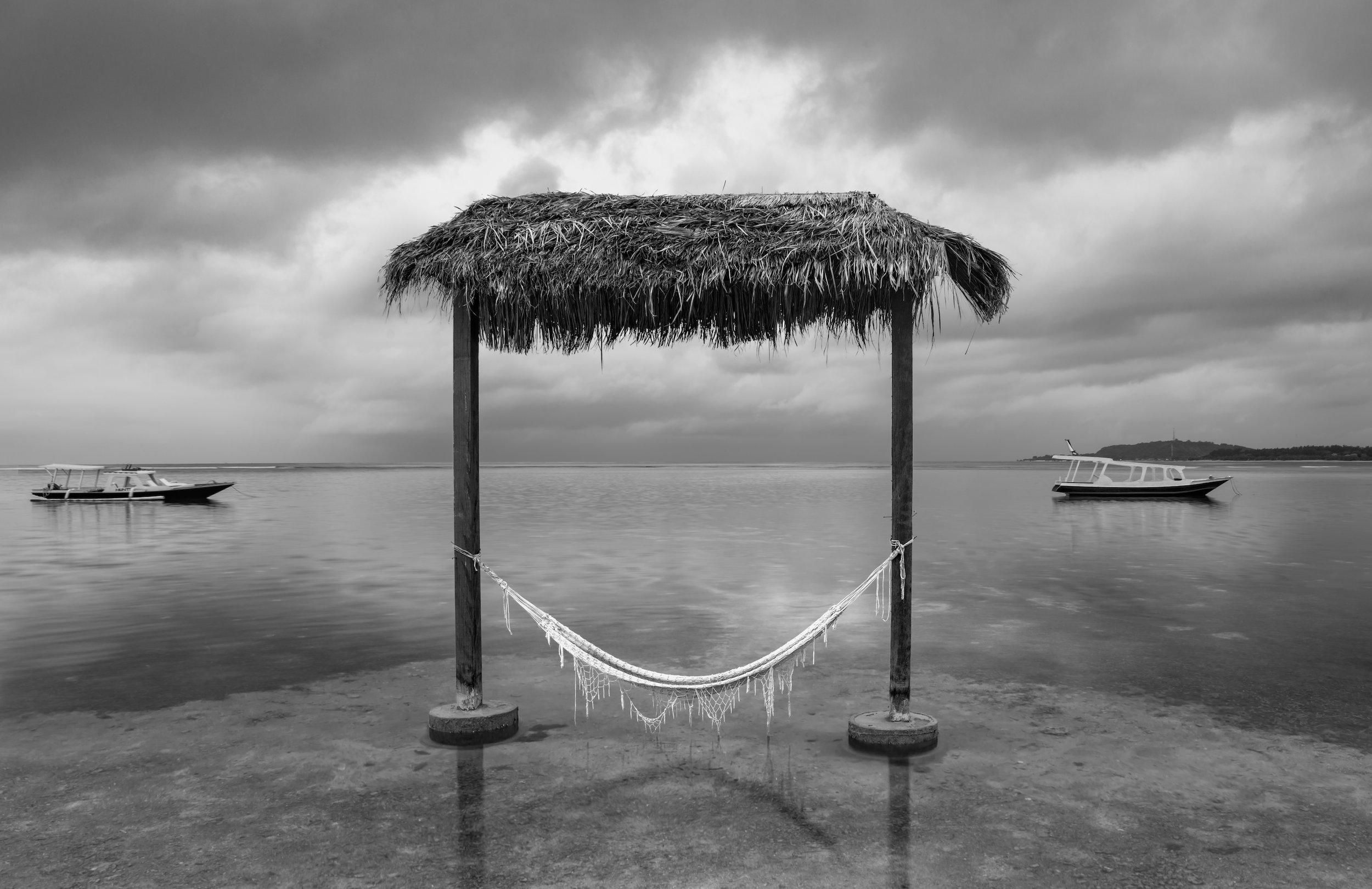 Black and white photograph from Gili Air, Bali, Indonesia. A Hammock hangs above the ocean shore on a cloudy day. Two boats float in the background.