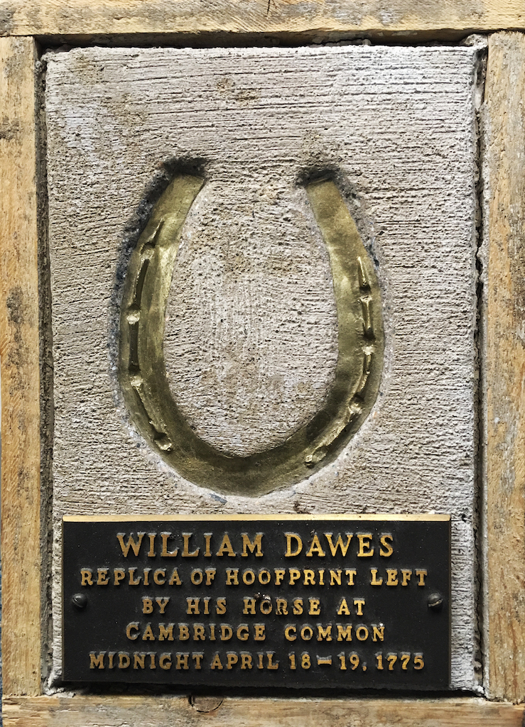 Bronze horseshoe embedded in sidewalk