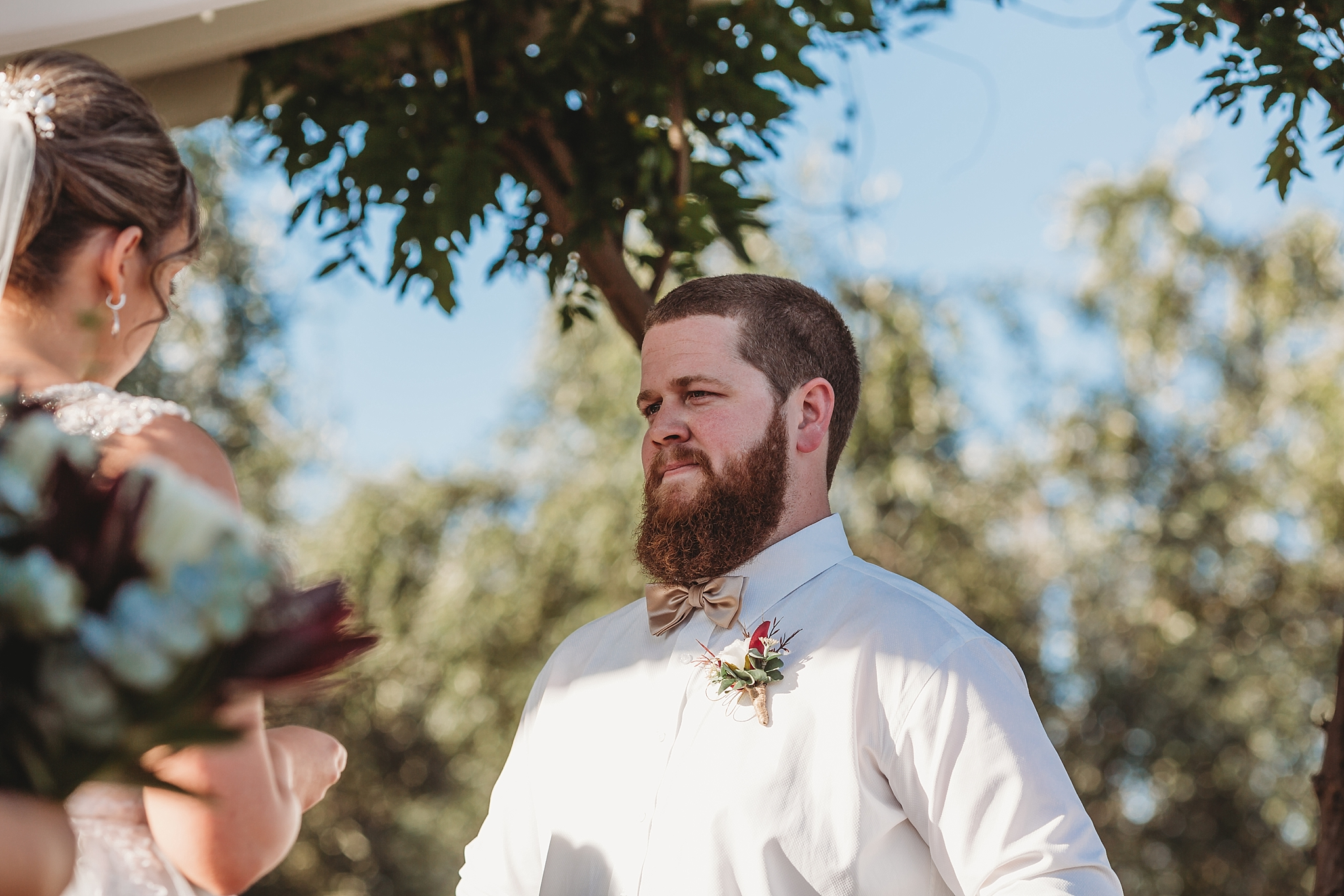 groom listening to bride say her vows