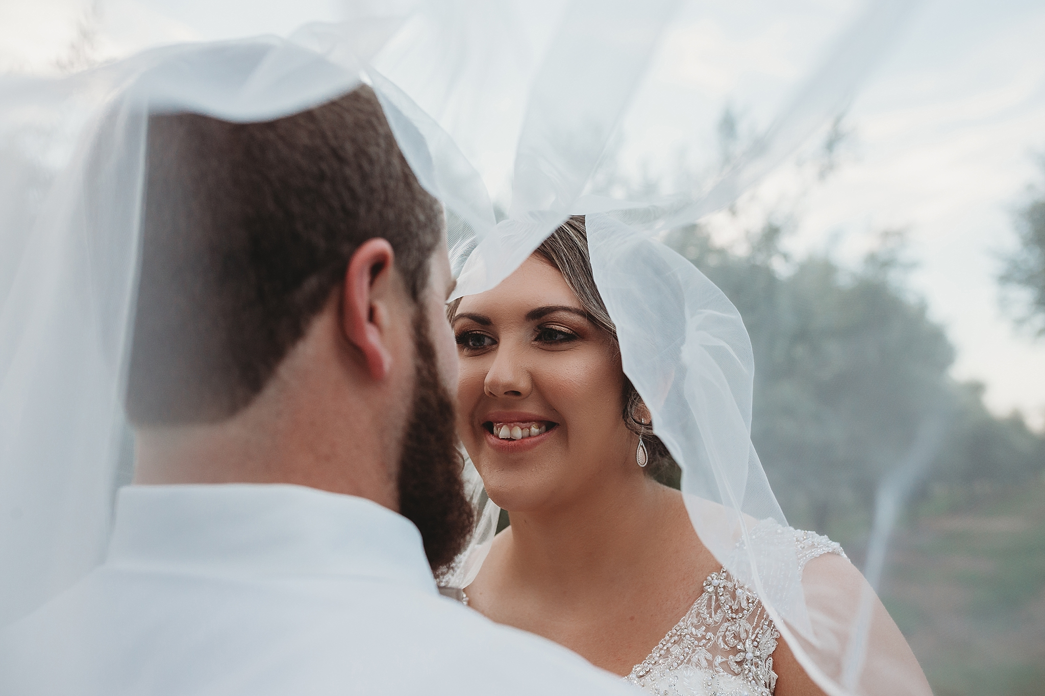bride and groom under the veil shot