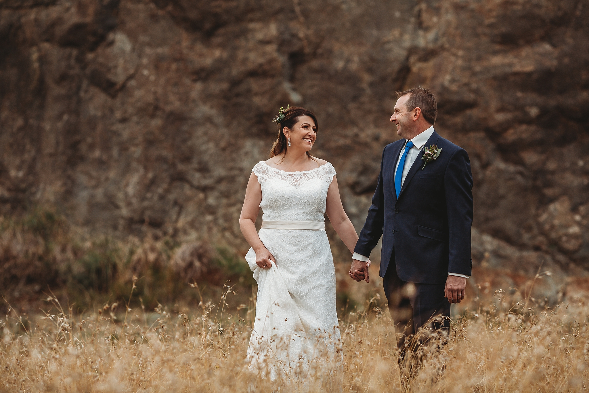 bride and groom walking in long grass at dookie quarry
