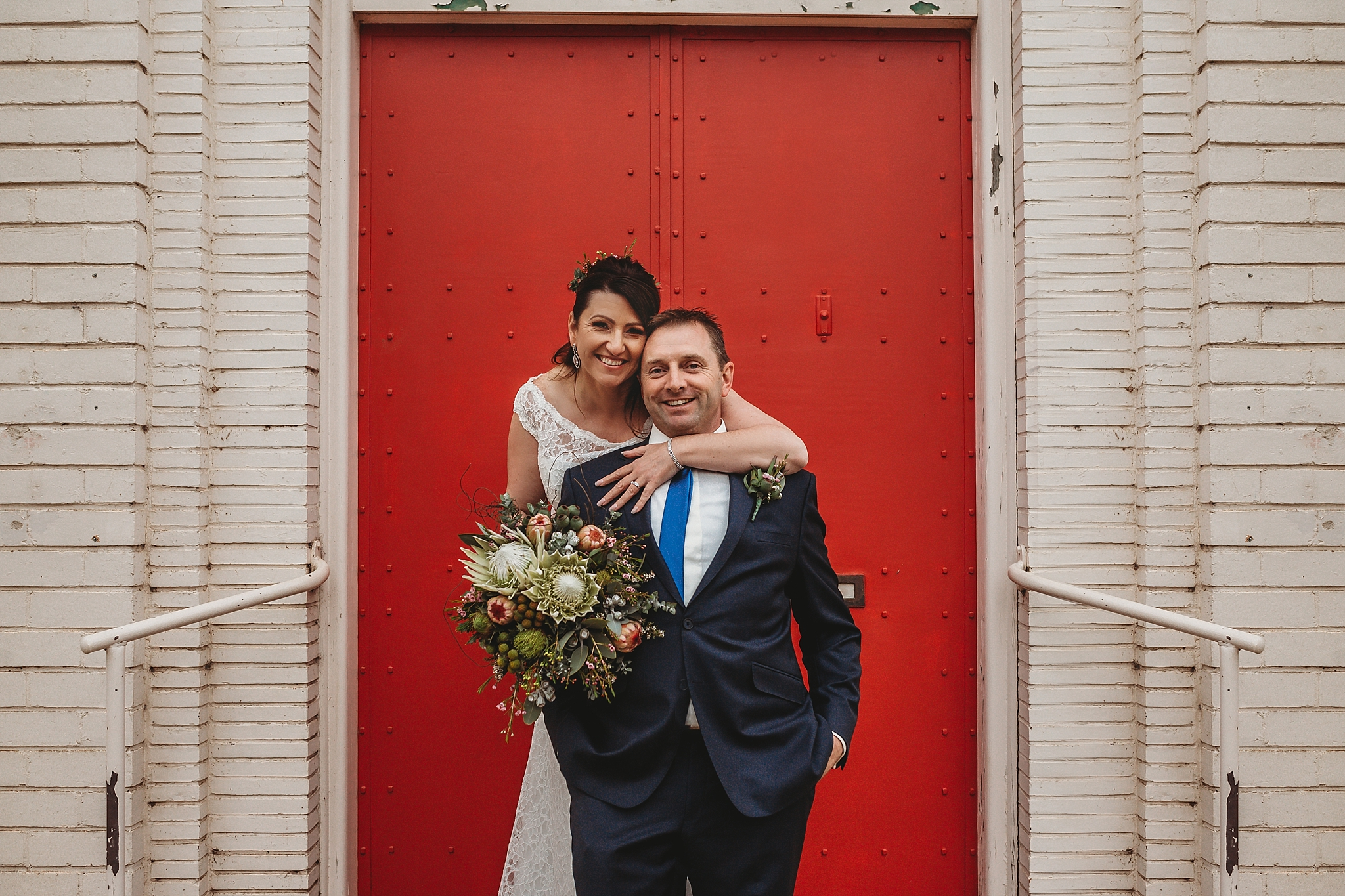 bride and groom on the steps of the dookie bank
