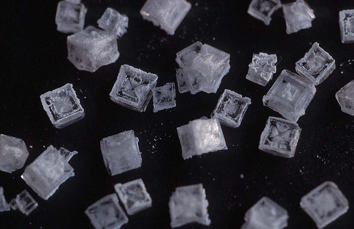 The regular shape of the salt crystals is caused by the arrangement of the atoms that make them up.