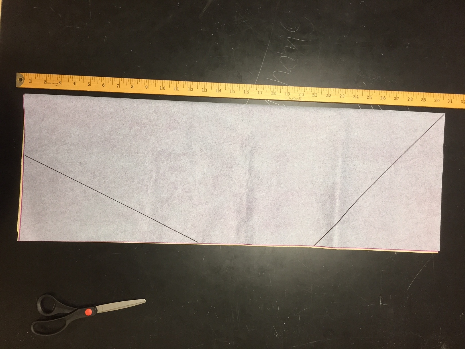 Fold four 20 x 30 sheets of tissue paper lengthwise. Mark cut lines as shown.    Make sure one cut line goes all the way to the fold and the other does not.