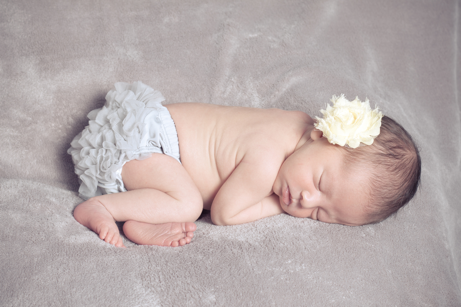 sleeping newborn baby girl with a gray ruffled diaper cover and a yellow flower in her dark hair, Clemmons newborn photographer