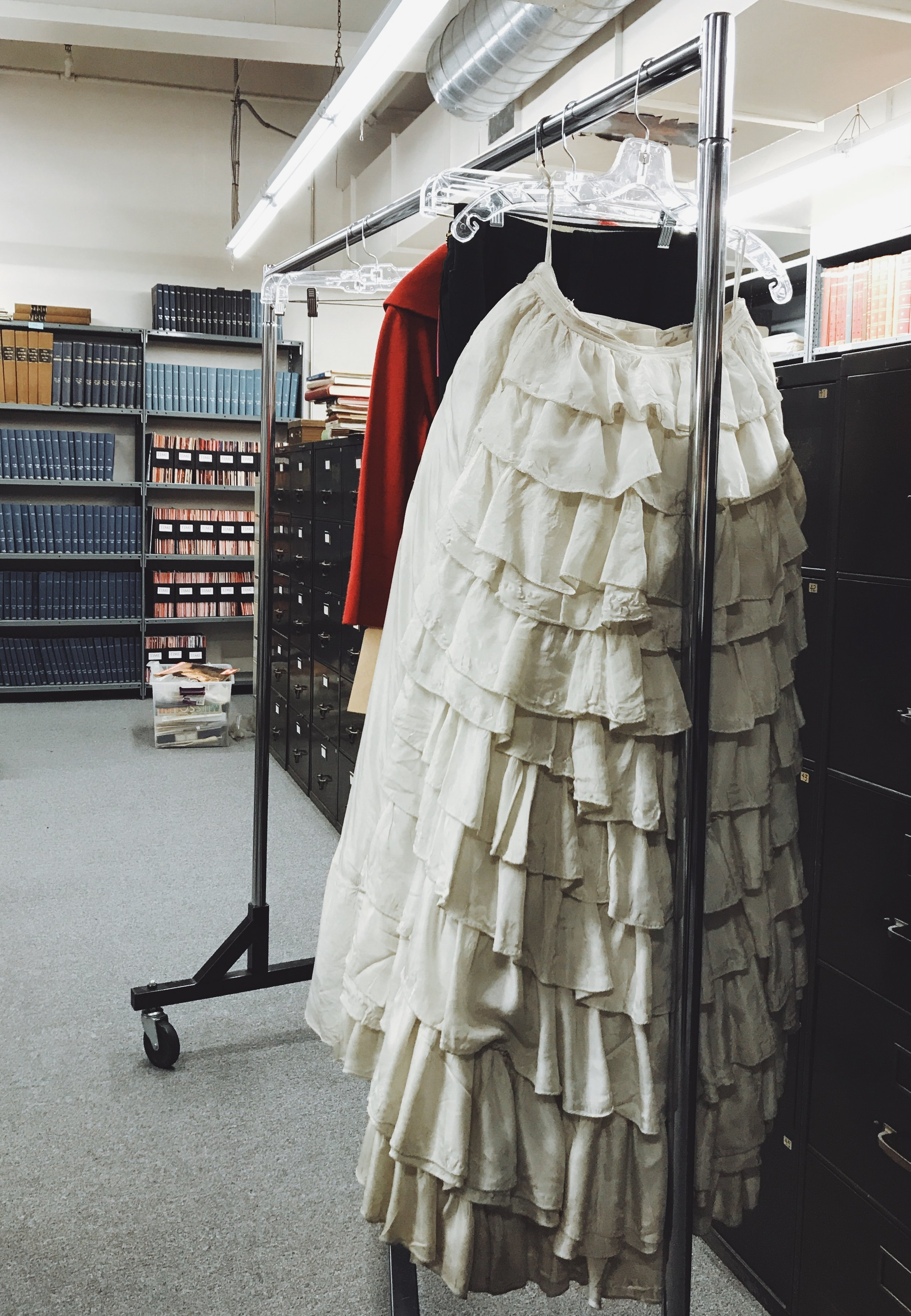 Clothes among the racks of books in the Western Costume research library.  Photo via  Finding Lost Angeles  (2018)