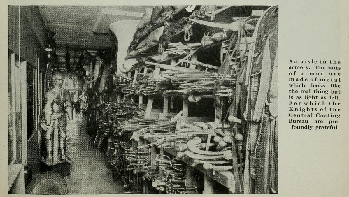"""""""An aisle in the armory. The suits of armor are made of metal which looks like the real thing but is light as felt. For which the Knights of Central Casting Bureau are profoundly grateful.""""  Photo via  Photoplay  (Feb. 1928)."""