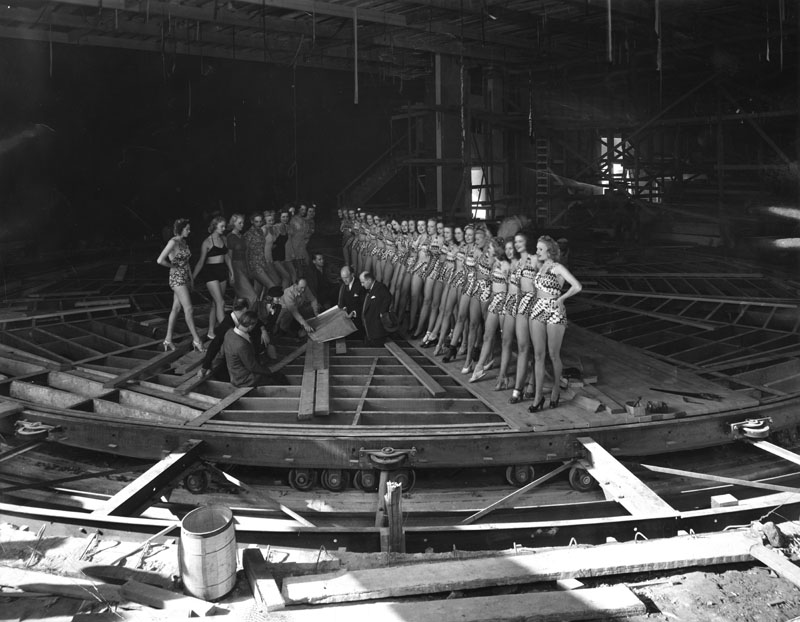 Earl Carroll with some of his aides and chorus girls examining construction of the moving stage. Photo via Los Angeles Public Library (1938).