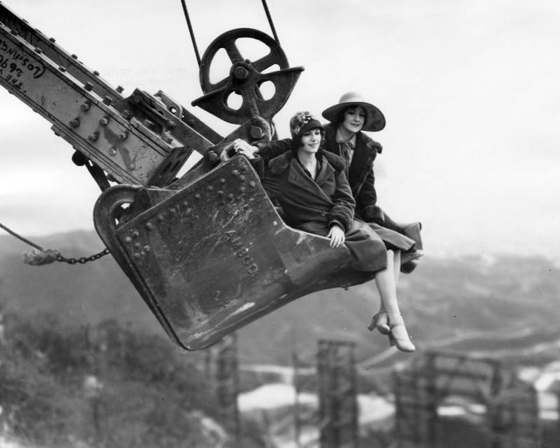 Publicity photo of women in a steam shovel above Hollywoodland. Photo via  Los Angeles Public Library  (1924)