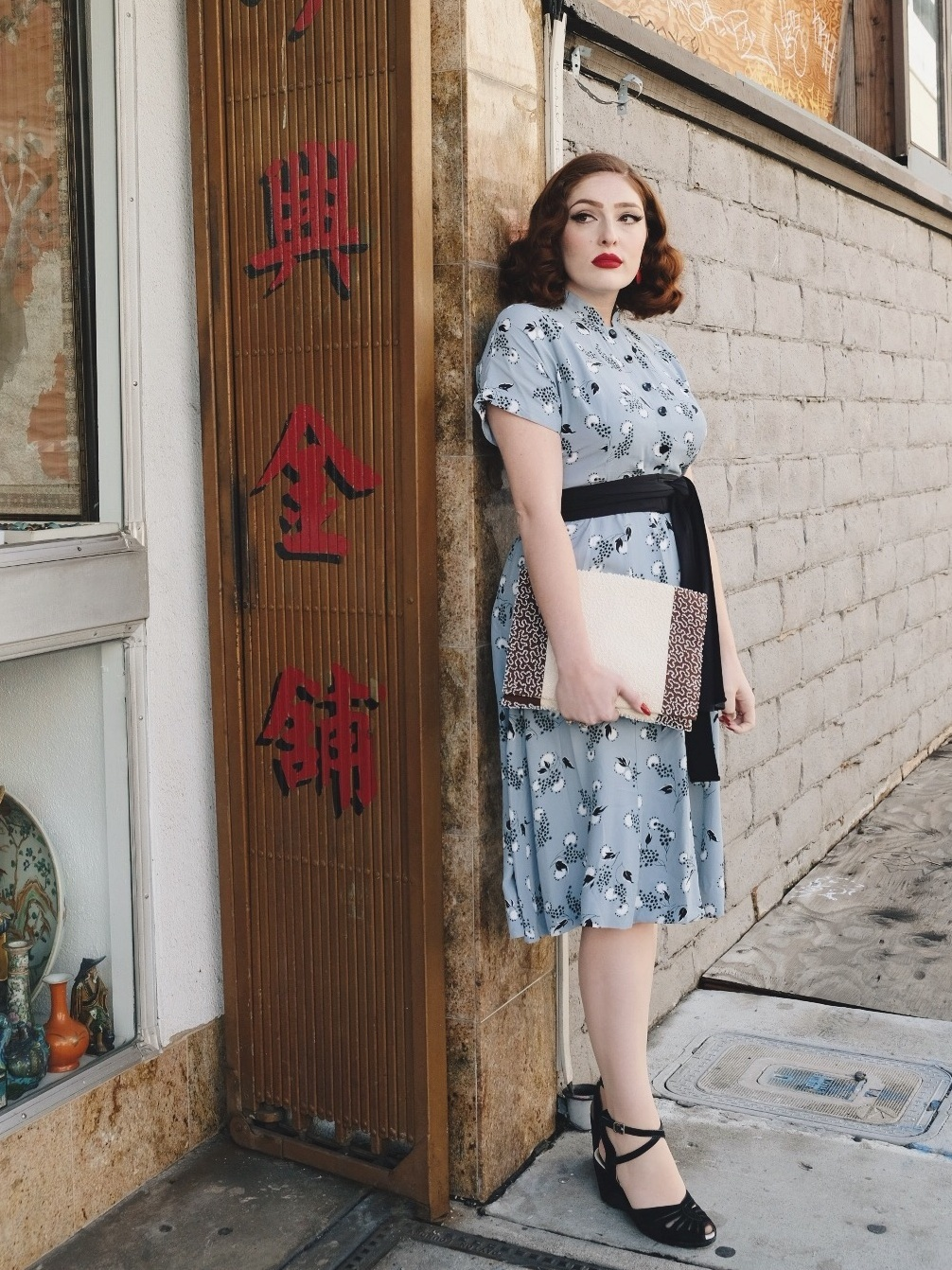 Woman in vintage blue dress standing by Chinatown storefront