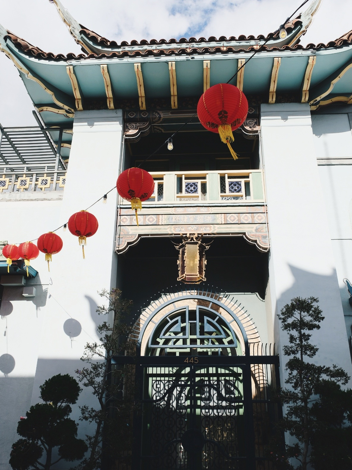 Blue building in Chinatown with string of red lanterns