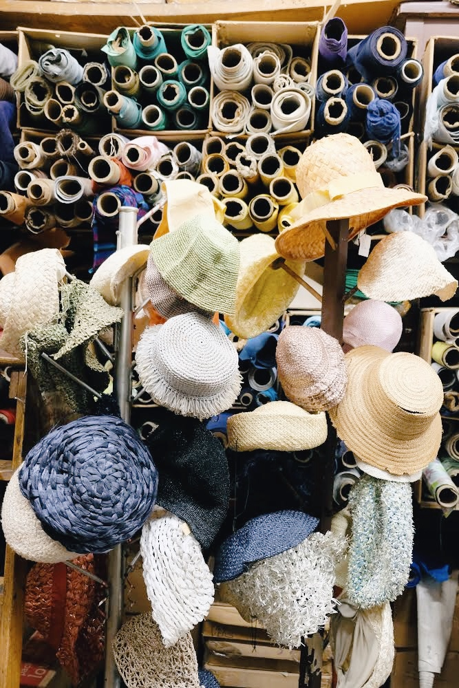 Hat rack display filled with hats in front of a wall of vintage fabric at California Millinery Supply Co. (2019)