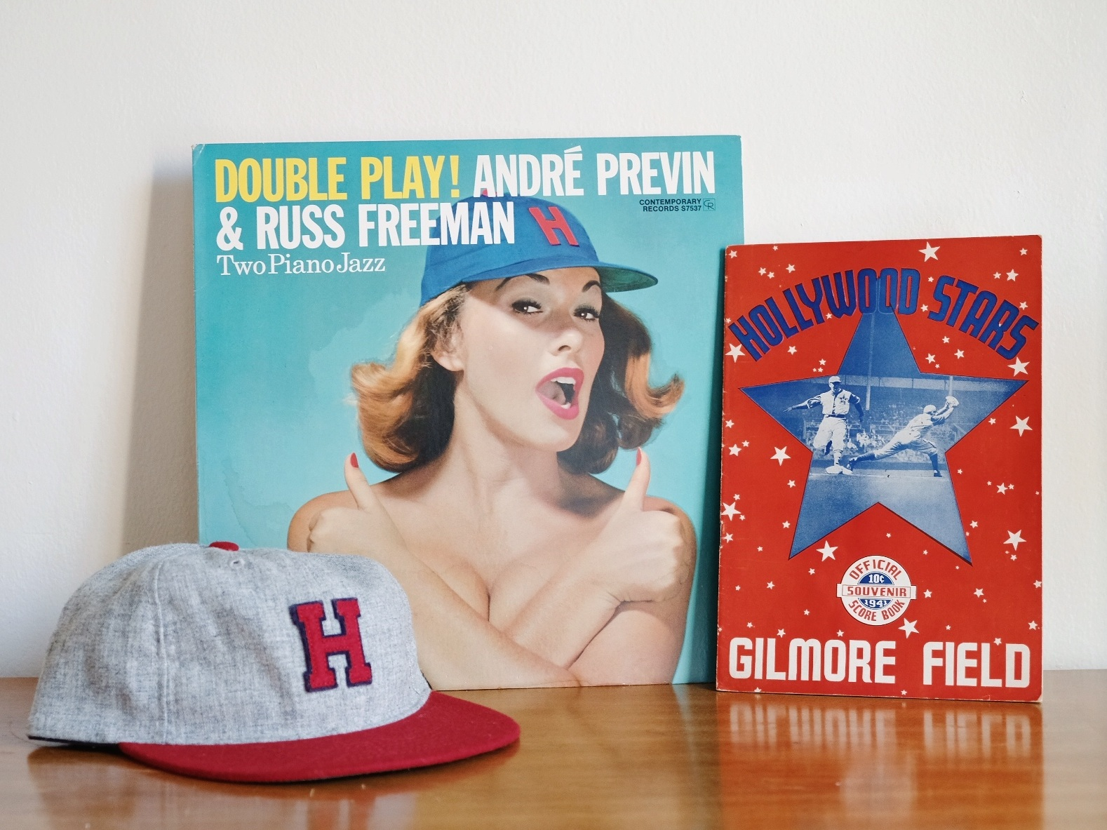 "From the FLA Archives (from left): a reproduction Hollywood Stars hat from  Ebbets Field Flannels , jazz album ""Double Play!"" (1957) featuring cover model wearing only a Hollywood Stars hat, and an official program from Gilmore Field (1941)."