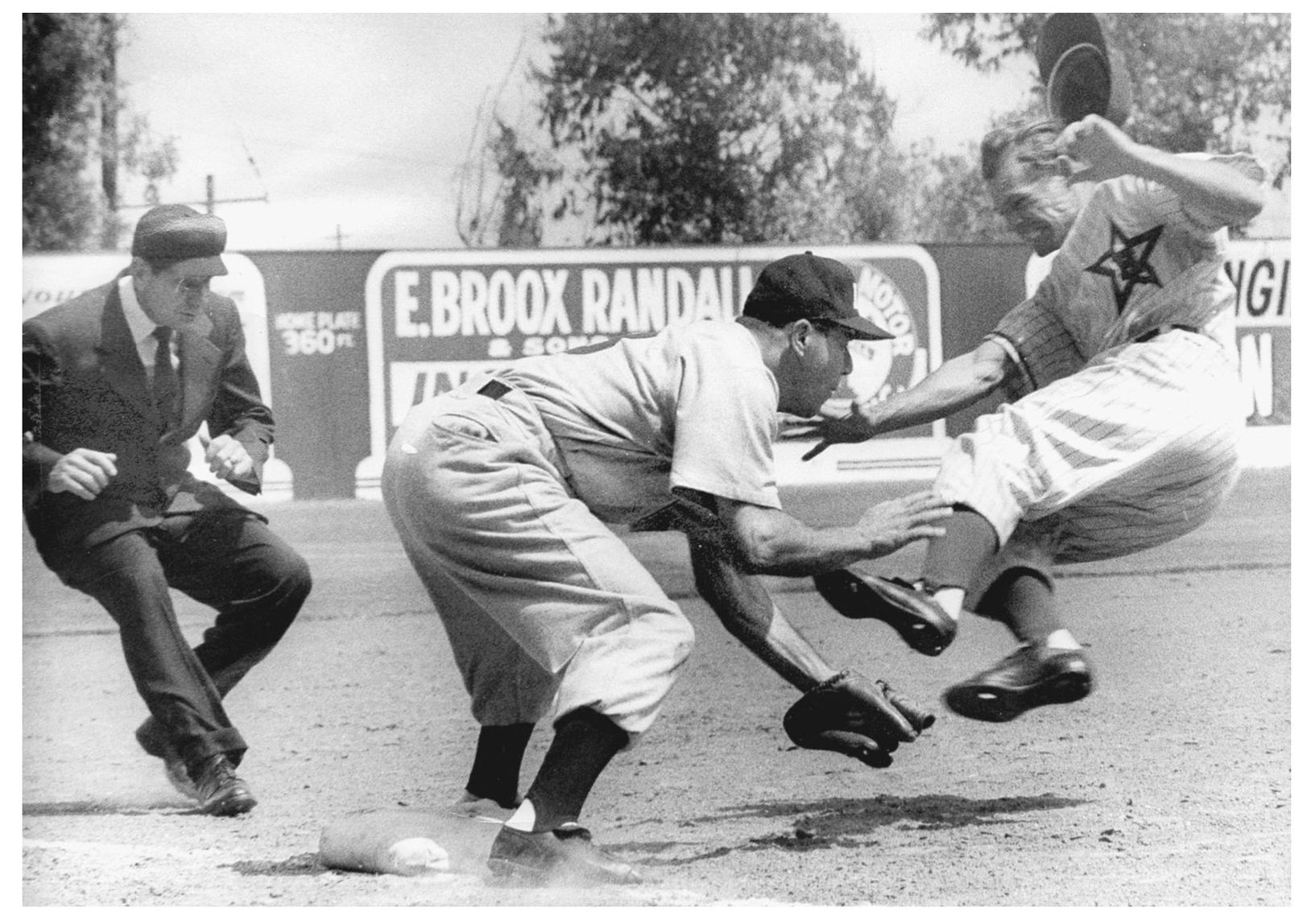 Hollywood Stars' Ted Beard, sliding spikes first into Angels' third baseman Murray Franklin, setting off a riot at Gilmore Field in 1953.