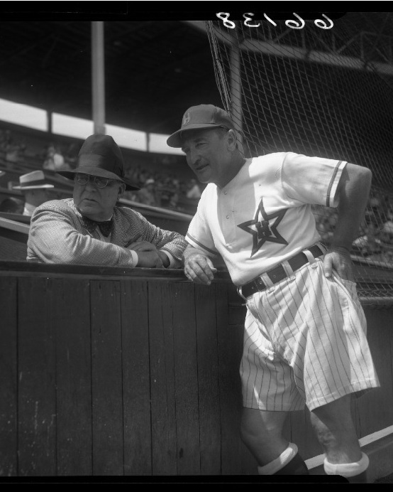 Stars manager Fred Haney talking with Branch Rickey, general manager of the Brooklyn Dodgers, while wearing their his shorts uniform. Photo via UCLA Library, LA Times Collection (1950).