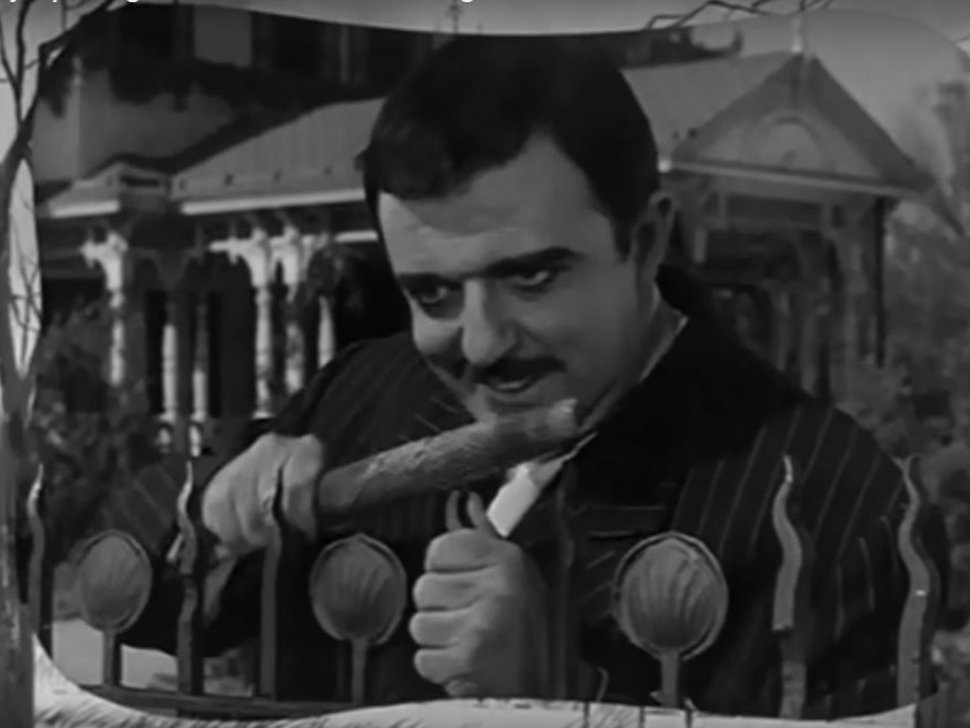 Gomez Addams in  The Addams Family  opening credits, with 21 Chester Place in the background. (MGM Television 1964)