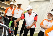 HMRT Member, Mohd Faizul, Chief Fuel Man of HMRT explaining about HMRT Race Car 27 to TOC students.  Image source:  Honda Malaysia