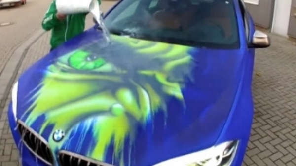 """The Hulk"" appears when hot water is being poured onto the car.   Image source:  https://nerdist.com/watch-a-bmw-turn-into-the-hulk-when-splashed-with-hot-water/"