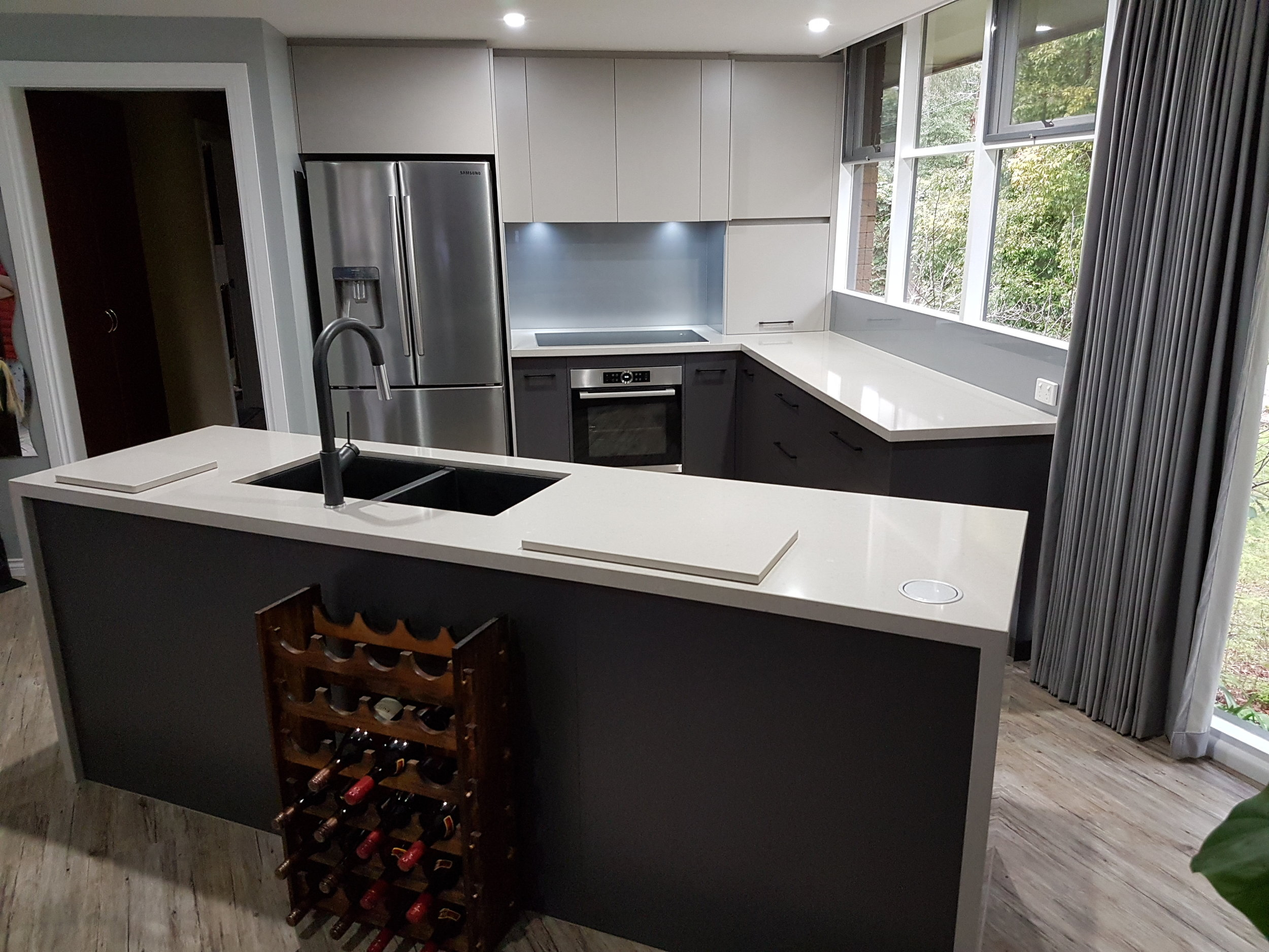 A beautifully positioned kitchen featuring an island bench with waterfall ends.