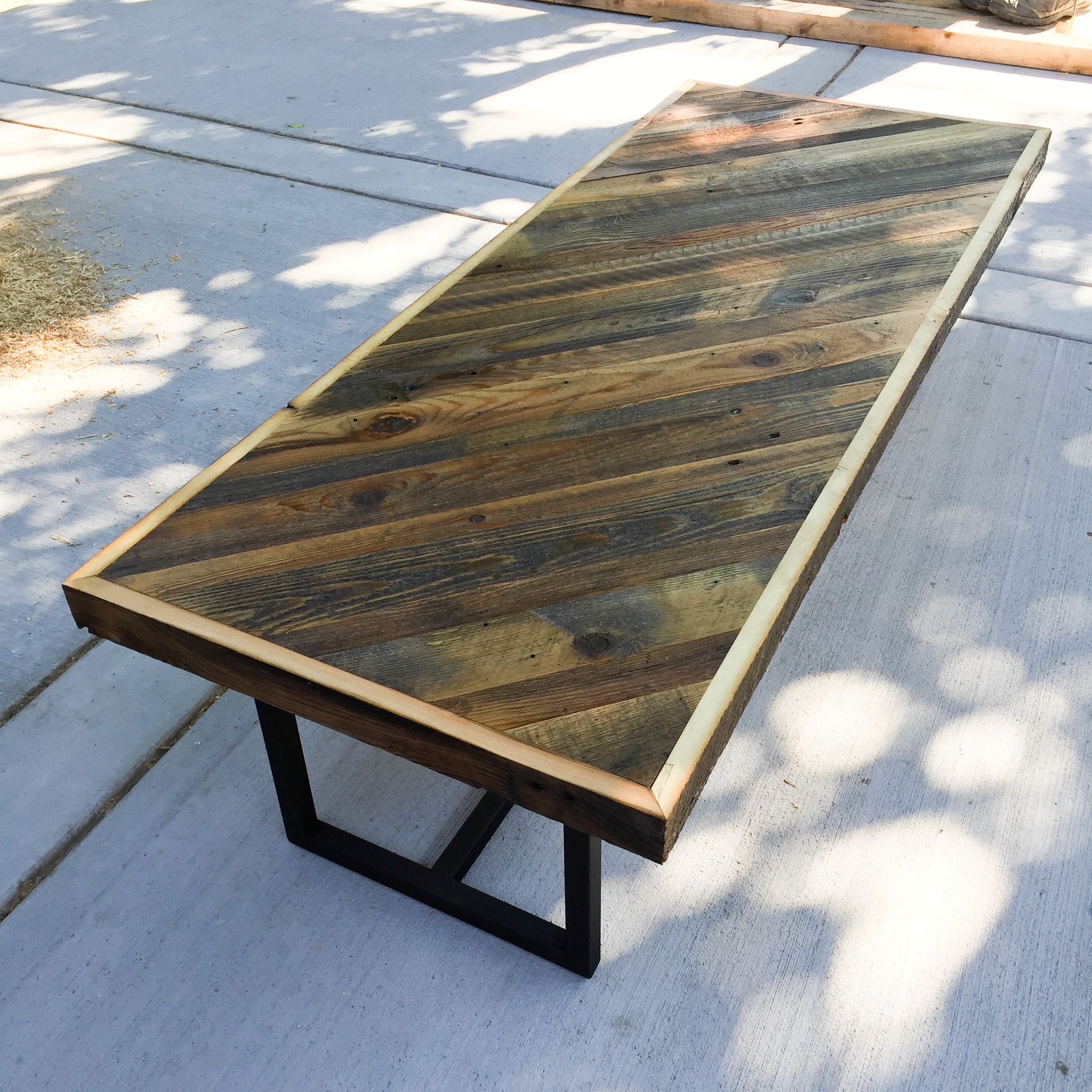 Reclaimed patterned table top with custom steel base.