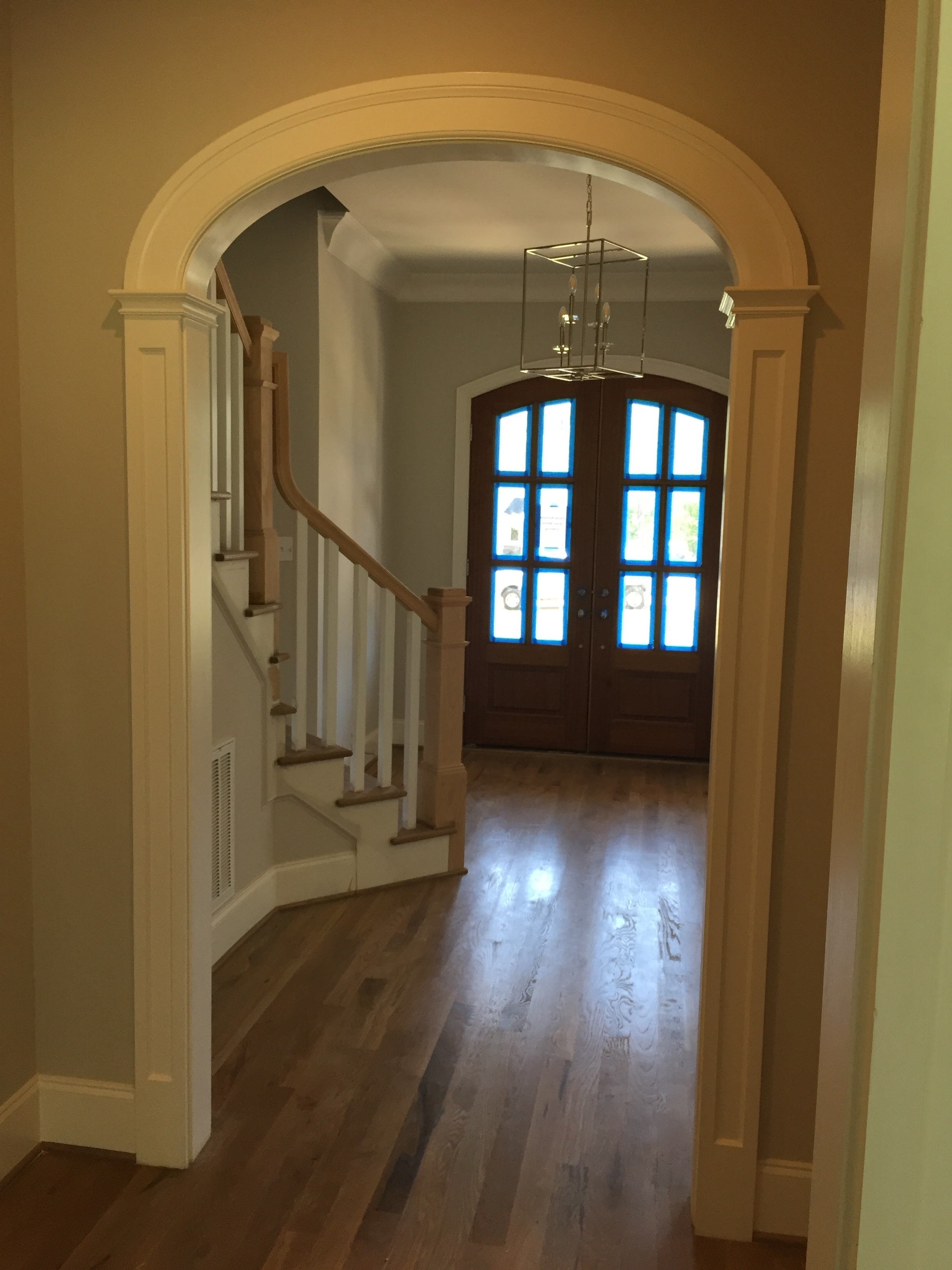 Farmhouse style arched door opening in foyer. panel column detail gives a current, clean look