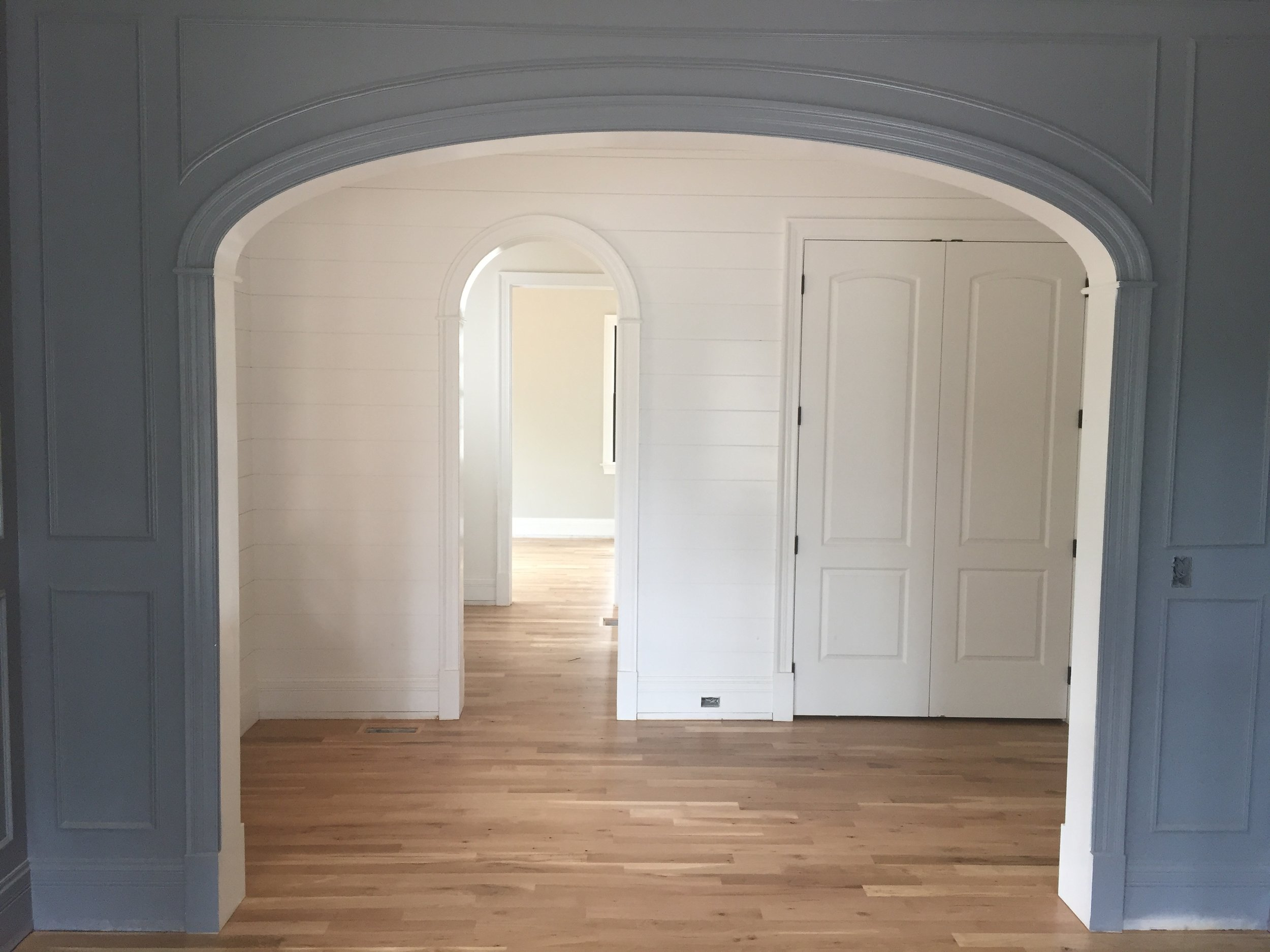 Dining room archway with arched wainscoting and shiplap walls