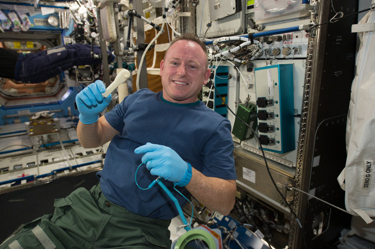 Astronaut Barry Wilmore with a 3D-printed ratchet aboard the International Space Station — the first part 3D printed in space. Image courtesy of NASA.