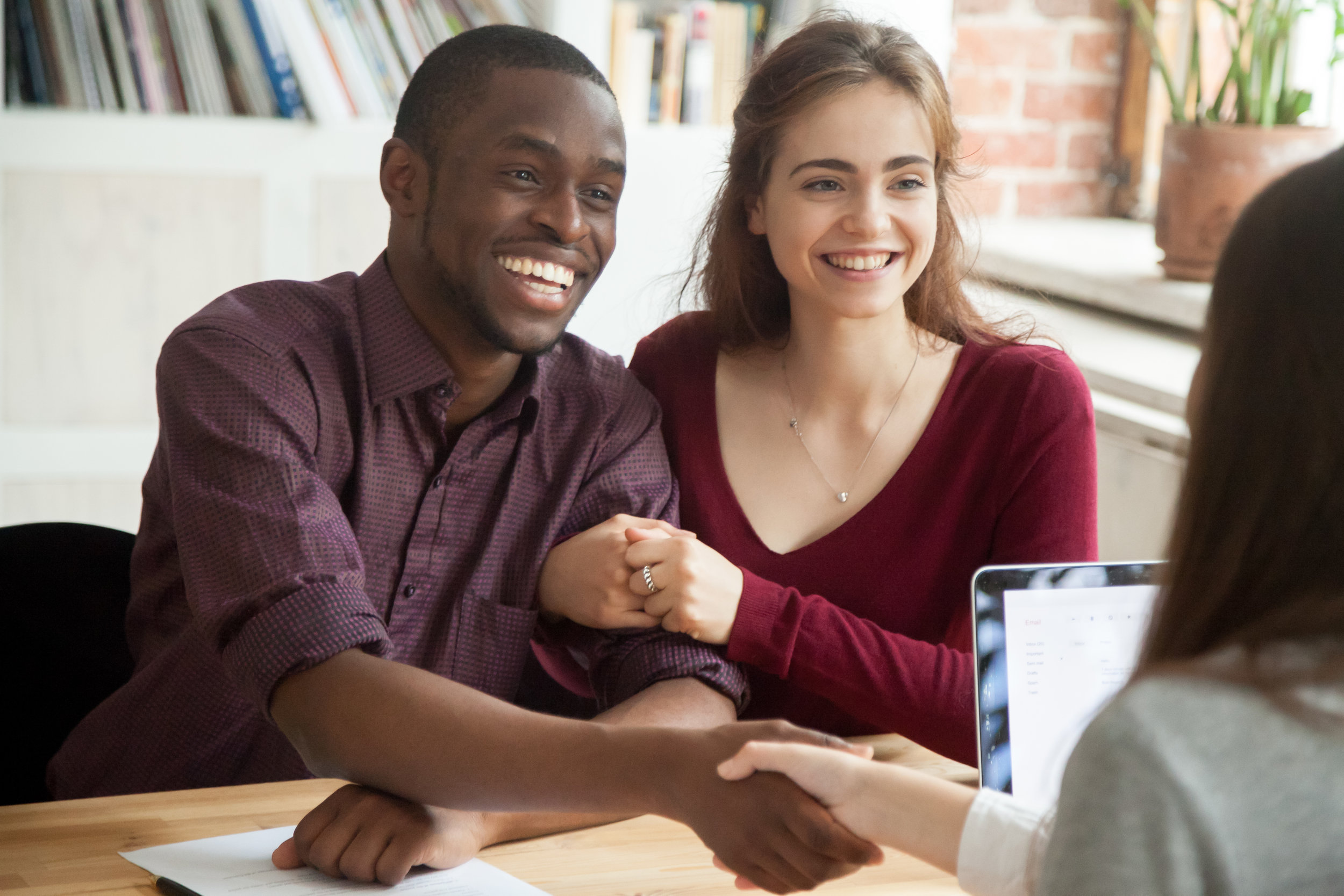 Smiling multiracial couple customers shaking hands with mortgage broker or financial advisor, happy attractive black and white family handshaking lawyer bank worker taking loan, making purchase deal