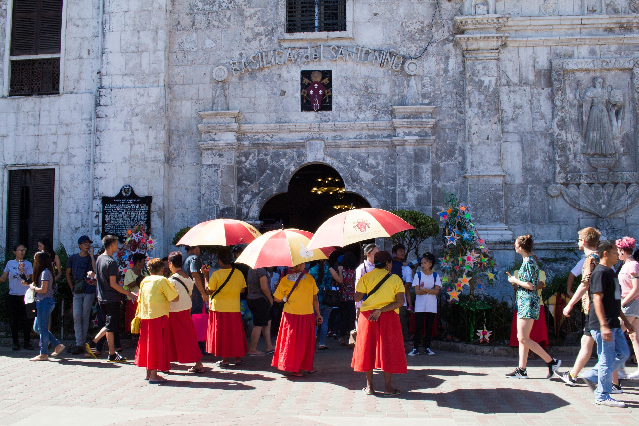 prayer candle vendors standing in front of santo niño basilica