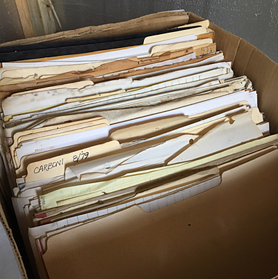 This is an example of typical box of archives; Manila folders and lined pads of paper, reprints of articles, newspaper clippings and random slips of paper, blank postcards and dry-cleaning receipts.