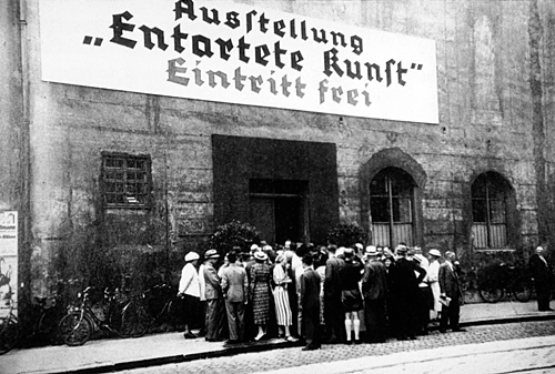"""People lining up to enter the """"Degenerate Art"""" (Entartete Kunst) exhibition in Munich sponsored by the Nazi government."""