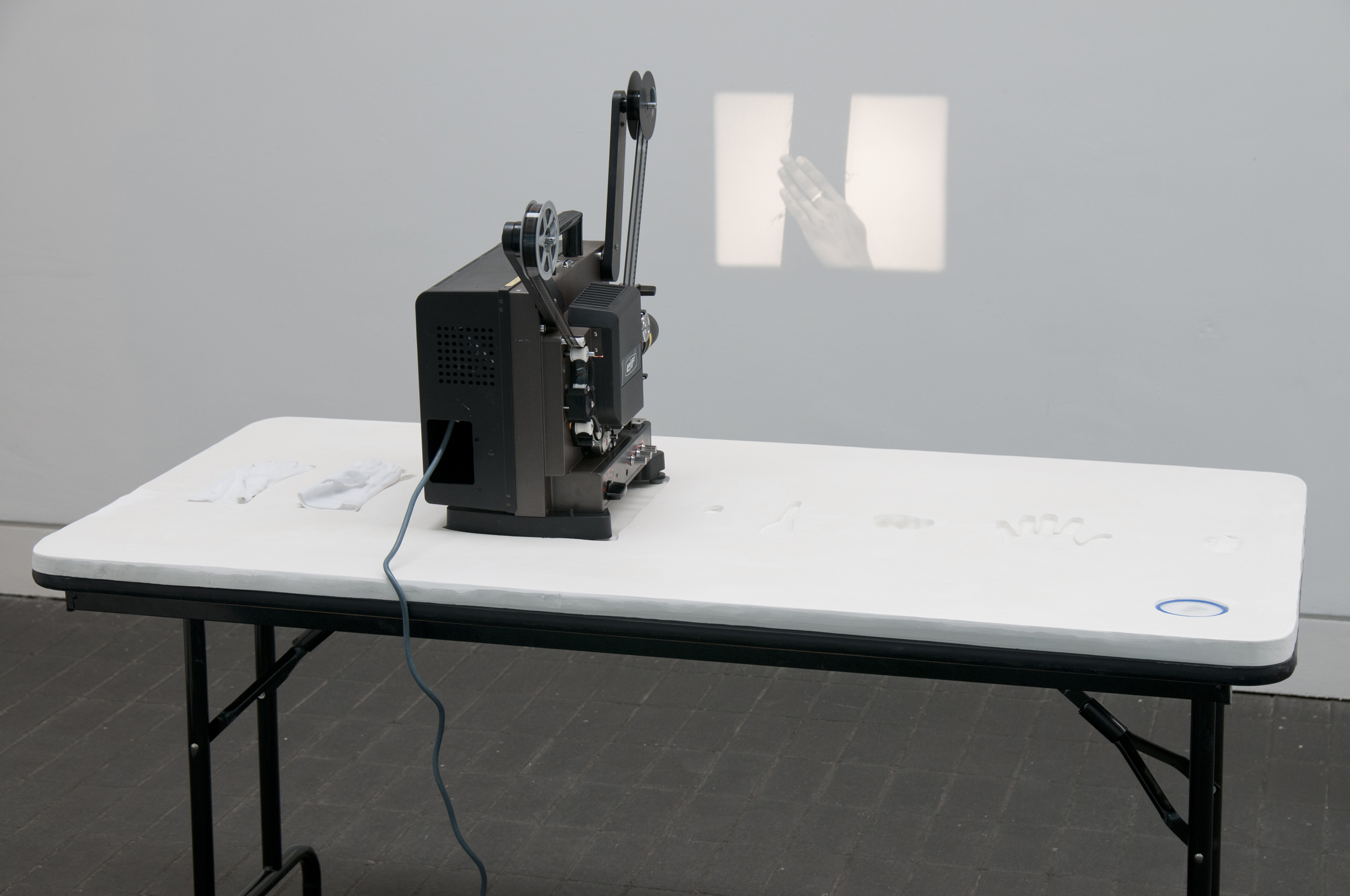 Currency   Performance  16mm film; Plaster table top  Exhibition view Jerwood Space, London  2014  Photo: thisistomorrow.info